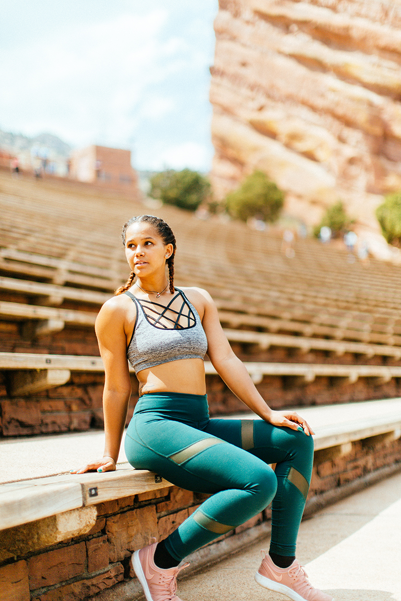 A beautiful young African American woman posing for a Red Rocks Amphitheater fitness session near Denver, Colorado wearing green leggings with a gray and black sports bra sitting on the wood steps