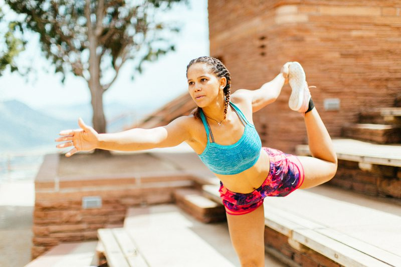 A beautiful young African American woman posing for a Red Rocks Amphitheater fitness session near Denver, Colorado wearing pink and purple workout shorts with a bright blue sports bra doing a yoga pose on the wood steps