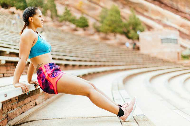 A beautiful young African American woman posing for a Red Rocks Amphitheater fitness session near Denver, Colorado wearing pink and purple workout shorts with a bright blue sports bra doing a dip on the wood steps