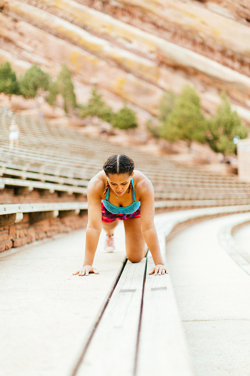 A beautiful young African American woman posing for a Red Rocks Amphitheater fitness session near Denver, Colorado wearing pink and purple workout shorts with a bright blue sports bra doing a plank on the wood steps