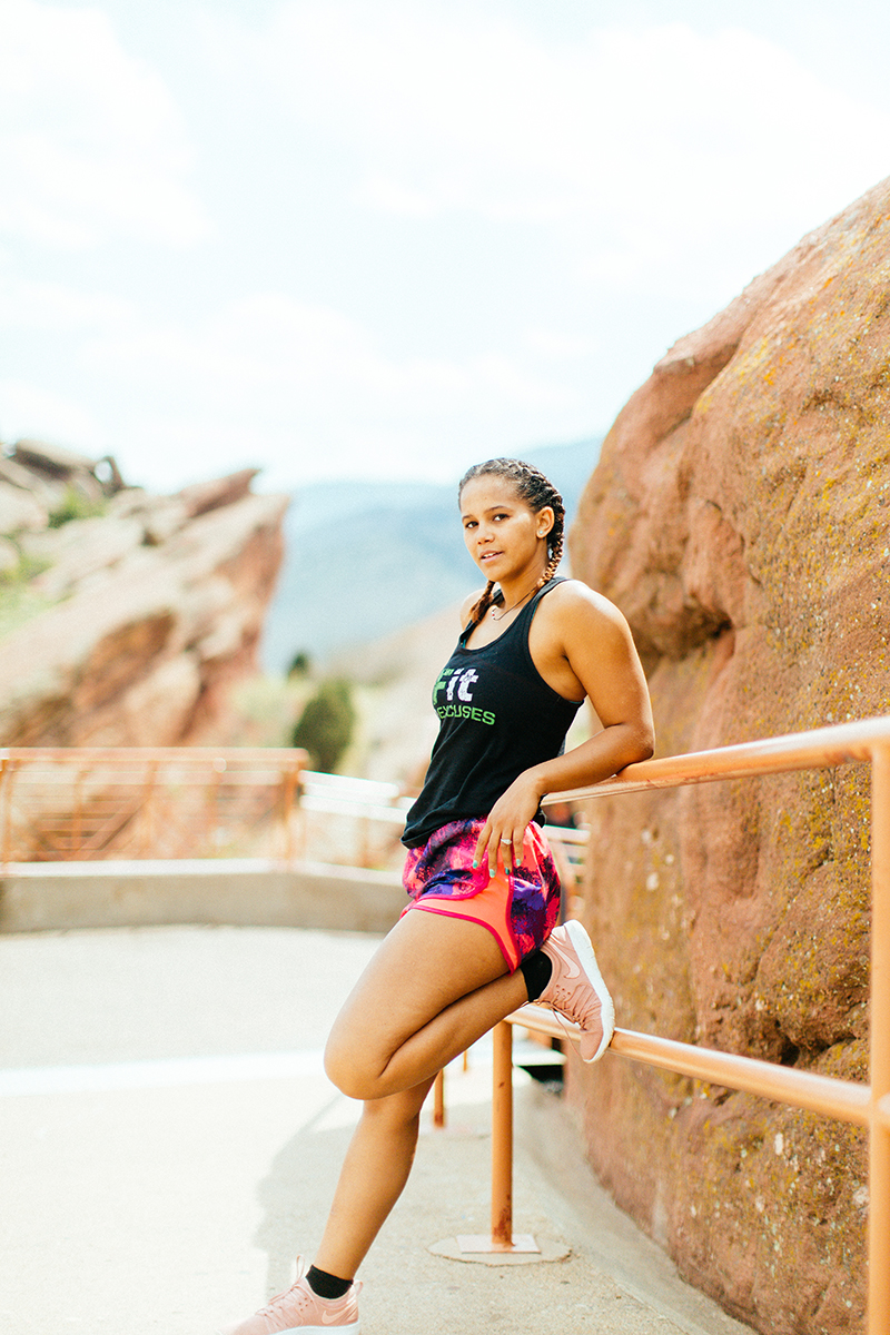 A beautiful young African American woman posing for a Red Rocks Amphitheater fitness session near Denver, Colorado wearing pink and purple workout shorts with a bright blue sports bra and black shirt leaning against the railing with the red rocks behind her