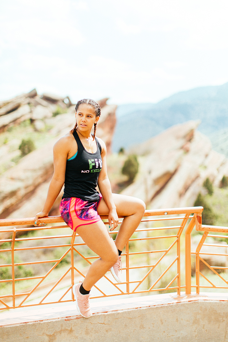 A beautiful young African American woman posing for a Red Rocks Amphitheater fitness session near Denver, Colorado wearing pink and purple workout shorts with a bright blue sports bra and black shirt sitting on the railing with the red rocks behind her