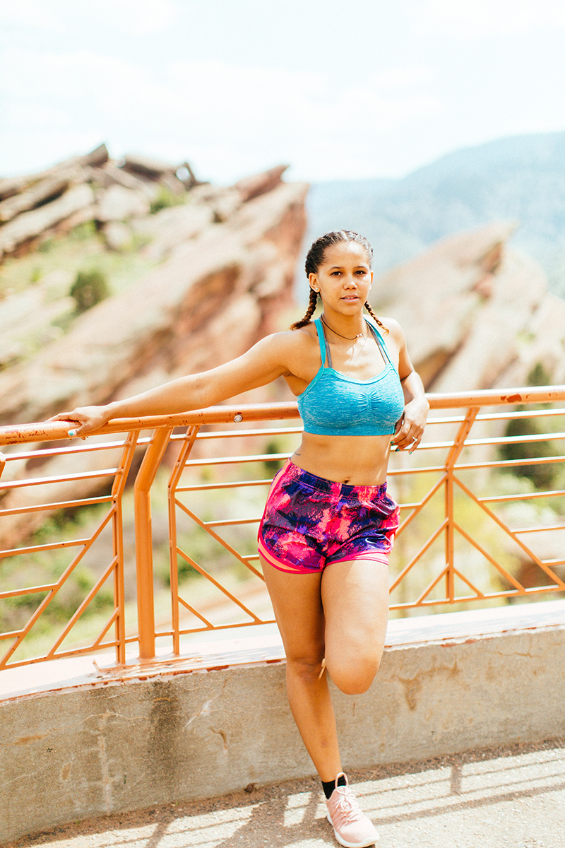 A beautiful young African American woman posing for a Red Rocks Amphitheater fitness session near Denver, Colorado wearing pink and purple workout shorts with a bright blue sports bra leaning against the railing with the red rocks behind her