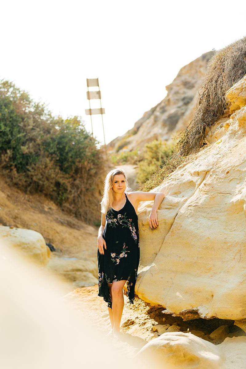 A beautiful young blonde woman poses for a Black's Beach boudoir photography session in San Diego, California wearing a black floral print dress leaning against a rock in a canyon near the ocean
