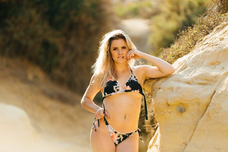 A beautiful young blonde woman poses for a Black's Beach boudoir photography session in San Diego, California wearing a black floral print bikini leaning against a rock in a canyon near the ocean