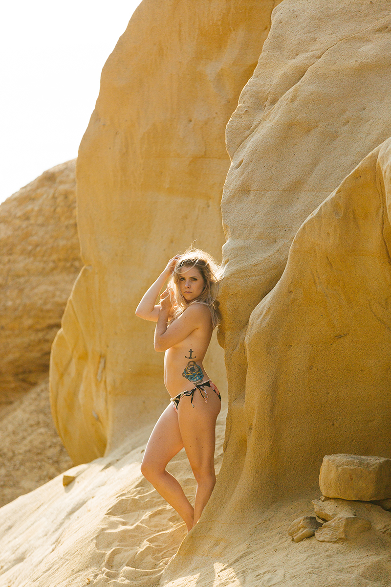 A beautiful young blonde woman poses topless for a Black's Beach boudoir photography session in San Diego, California wearing a black floral print bikini leaning against a rock in a canyon near the ocean