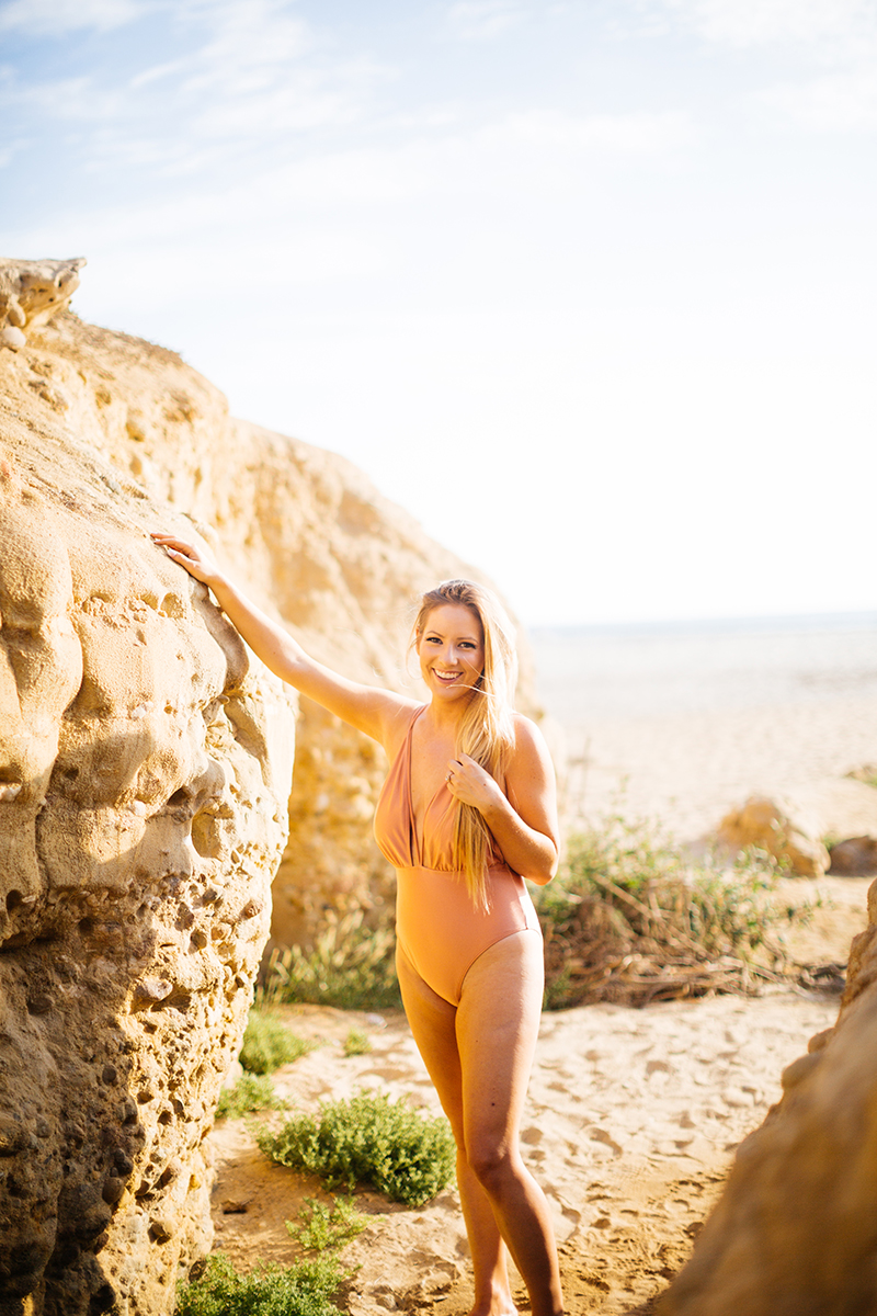A beautiful young blonde woman poses for a Black's Beach boudoir photography session in San Diego, California wearing an orange bathing suit leaning against rocks in a canyon near the beach