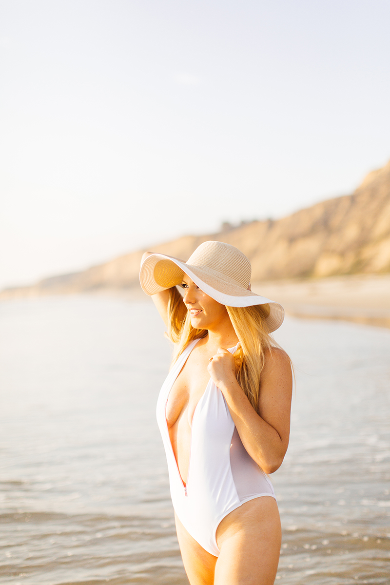A beautiful young blonde woman poses for a Black's Beach boudoir photography session in San Diego, California wearing a white bathing suit and a straw hat standing on the beach as the tide comes in at sunset