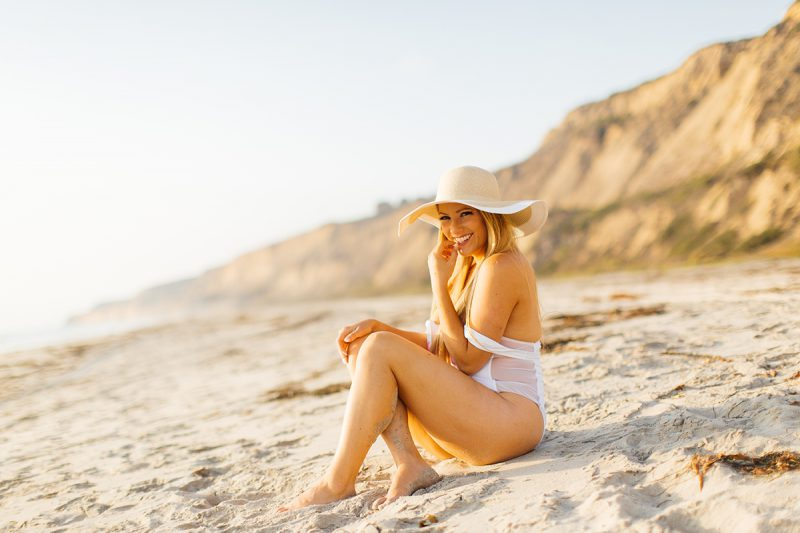 A beautiful young blonde woman poses for a Black's Beach boudoir photography session in San Diego, California wearing a white bathing suit and a straw hat sitting on the beach as the tide comes in at sunset