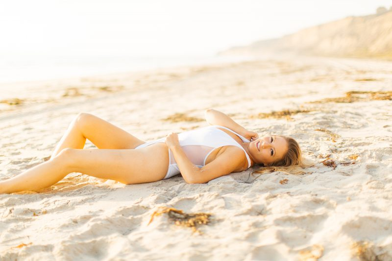 A beautiful young blonde woman poses for a Black's Beach boudoir photography session in San Diego, California wearing a white bathing suit laying on the beach as the tide comes in at sunset