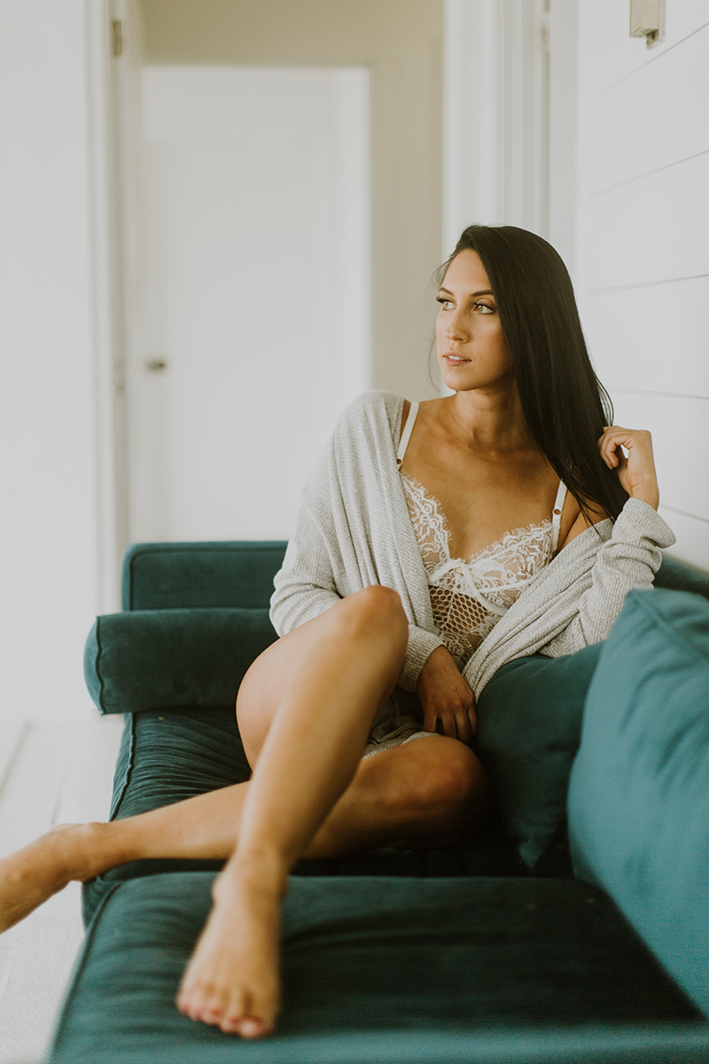 A beautiful young brunette woman poses for Denver Photo Collective boudoir photos in Lakewood, Colorado wearing a white lingerie body suit and a gray sweater sitting on a green couch in a white room