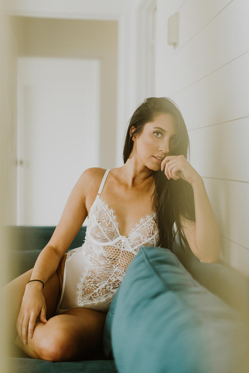A beautiful young brunette woman poses for Denver Photo Collective boudoir photos in Lakewood, Colorado wearing a white lingerie body suit sitting on a green couch in a white room