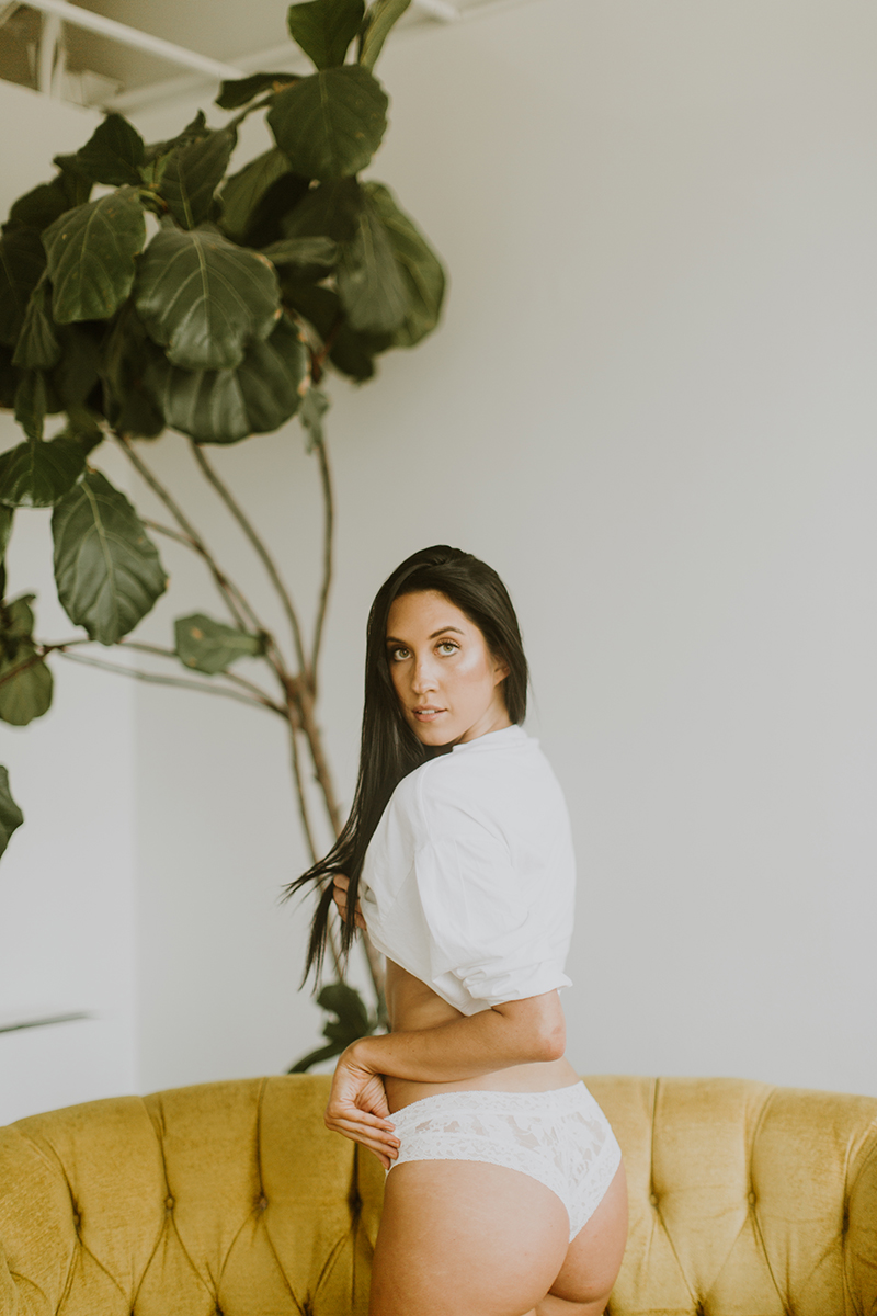 A beautiful young brunette woman poses for Denver Photo Collective boudoir photos in Lakewood, Colorado wearing a white shirt and white underwear on a yellow couch in a white room