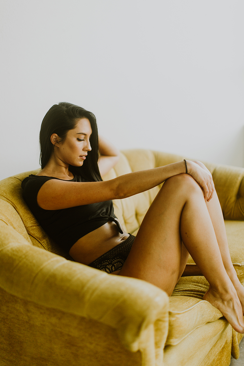 A beautiful young brunette woman poses for Denver Photo Collective boudoir photos in Lakewood, Colorado wearing a black shirt and black underwear sitting on a yellow couch
