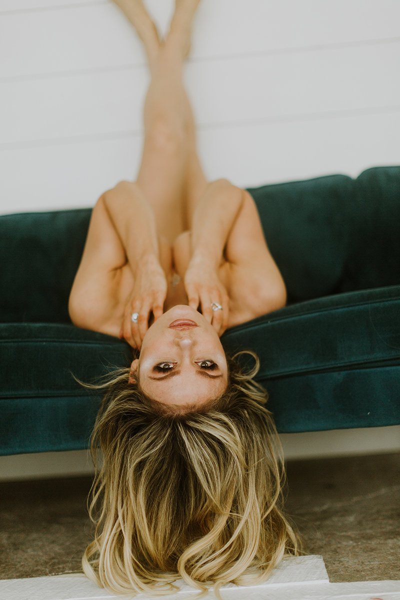 A beautiful young blonde woman poses topless for some Denver Photo Collective boudoir photos in Lakewood, Colorado wearing gray Calvin Klein underwear laying on a green couch against a white wall