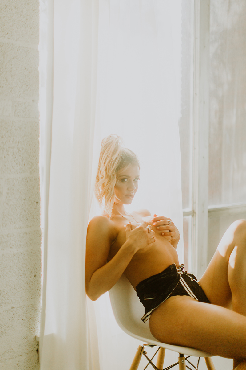 A beautiful young blonde woman poses topless for some Denver Photo Collective boudoir photos in Lakewood, Colorado wearing black shorts sitting on a stool in front of a window with curtains