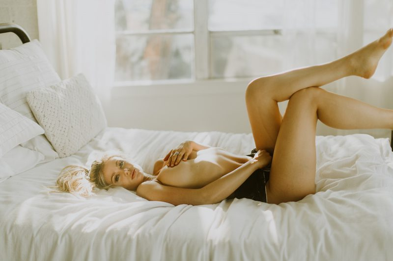 A beautiful young blonde woman poses topless for some Denver Photo Collective boudoir photos in Lakewood, Colorado wearing black shorts laying on a white bed in front of a window with curtains