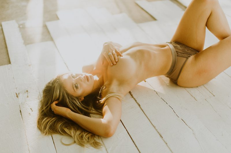 A beautiful young blonde woman poses topless for some Denver Photo Collective boudoir photos in Lakewood, Colorado wearing green underwear laying on a white wood floor with sunlight beaming in behind her