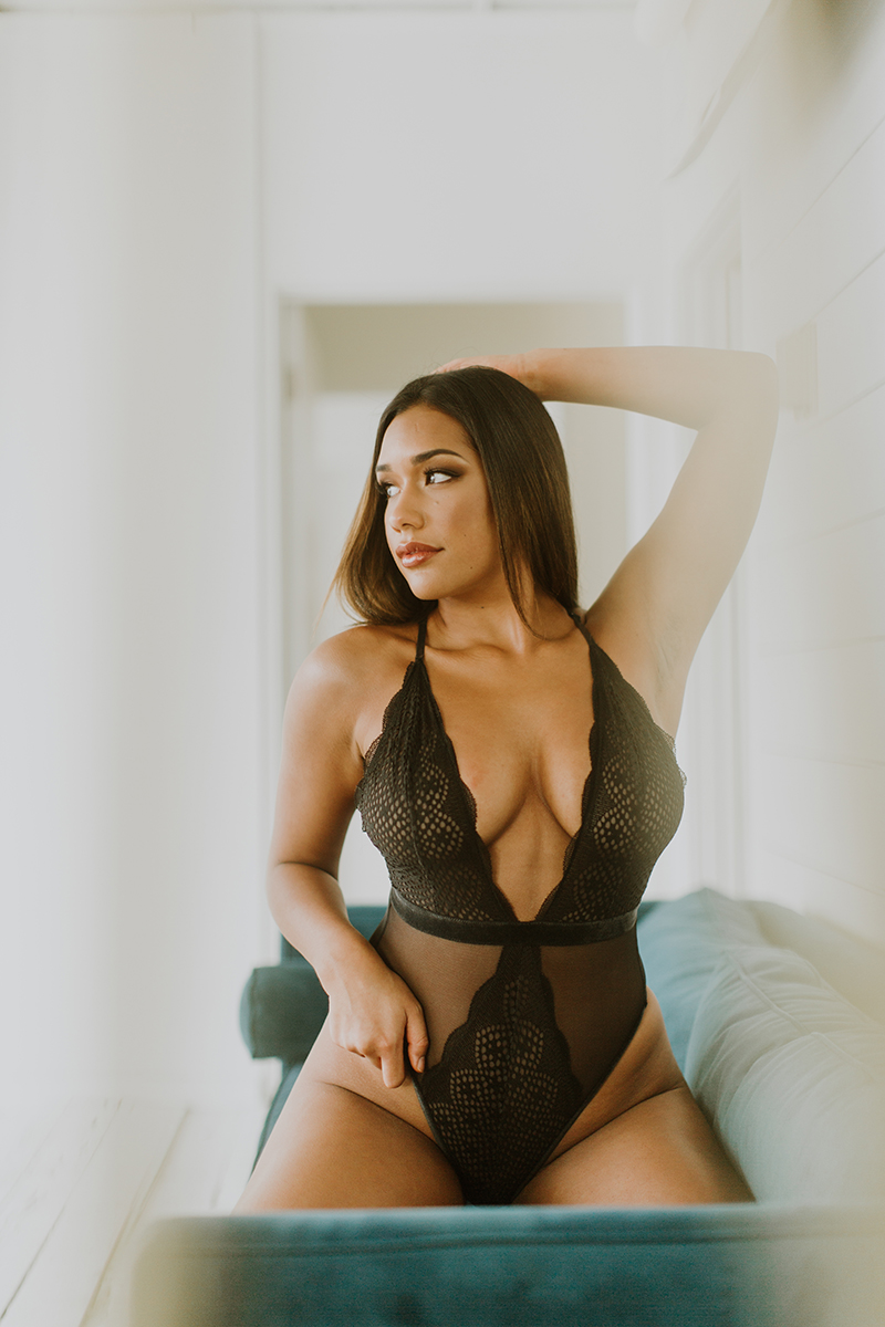 A beautiful young brunette woman poses for a Denver Photo Collective boudoir photography session in Lakewood, Colorado wearing black lingerie while kneeling on a green couch in a white room