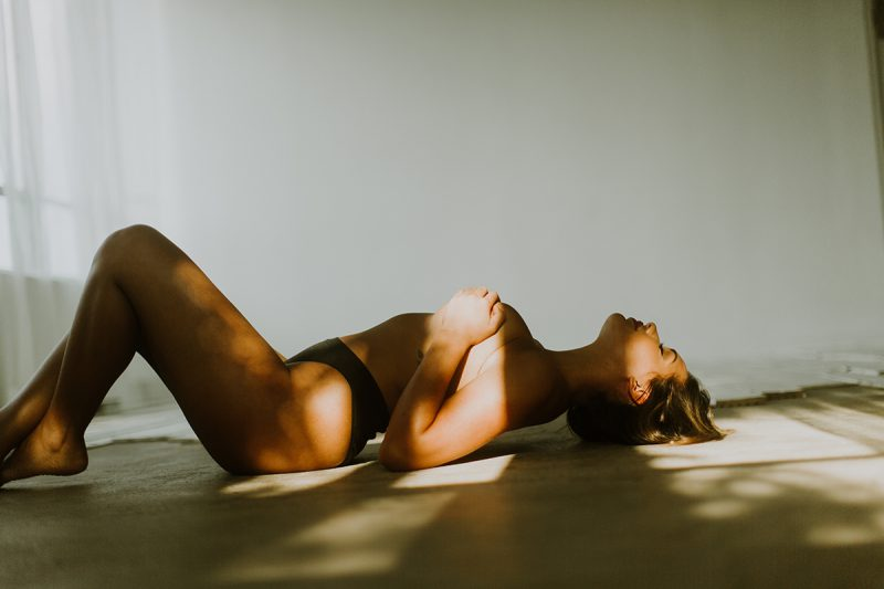A beautiful young brunette woman poses topless for a Denver Photo Collective boudoir photography session in Lakewood, Colorado wearing black underwear while laying on a concrete floor in a white room