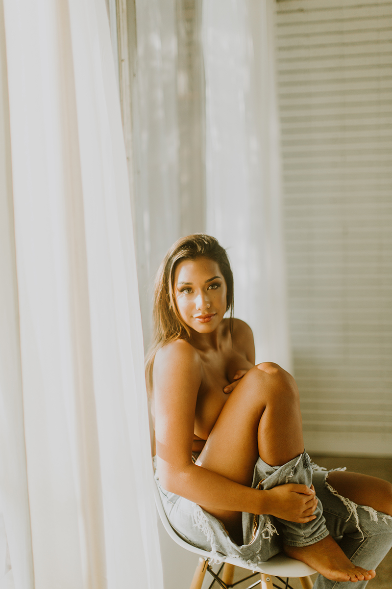 A beautiful young brunette woman poses topless for a Denver Photo Collective boudoir photography session in Lakewood, Colorado wearing ripped jeans while sitting on a wood stool in front of a window in a white room