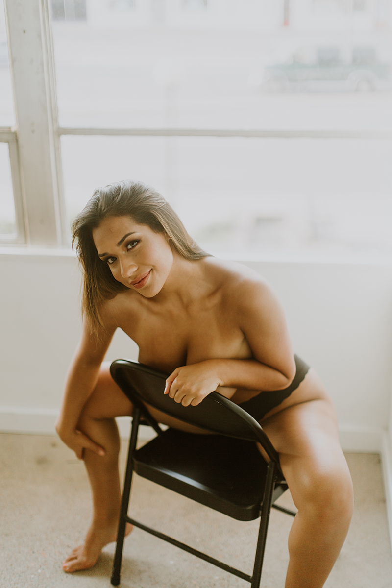 A beautiful young brunette woman poses topless for a Denver Photo Collective boudoir photography session in Lakewood, Colorado wearing black underwear while sitting on a black collapsable chair next to a window in a white room