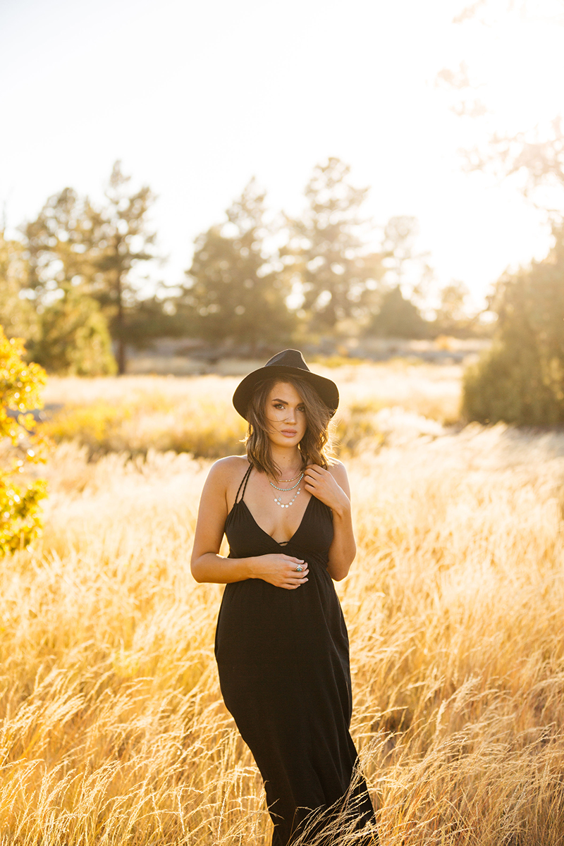 A beautiful young brunette woman poses for a Castlewood Canyon State Park boudoir photography session near Castle Rock, Colorado wearing a black dress and a black bohemian hat in the middle of a dry grass field at sunset