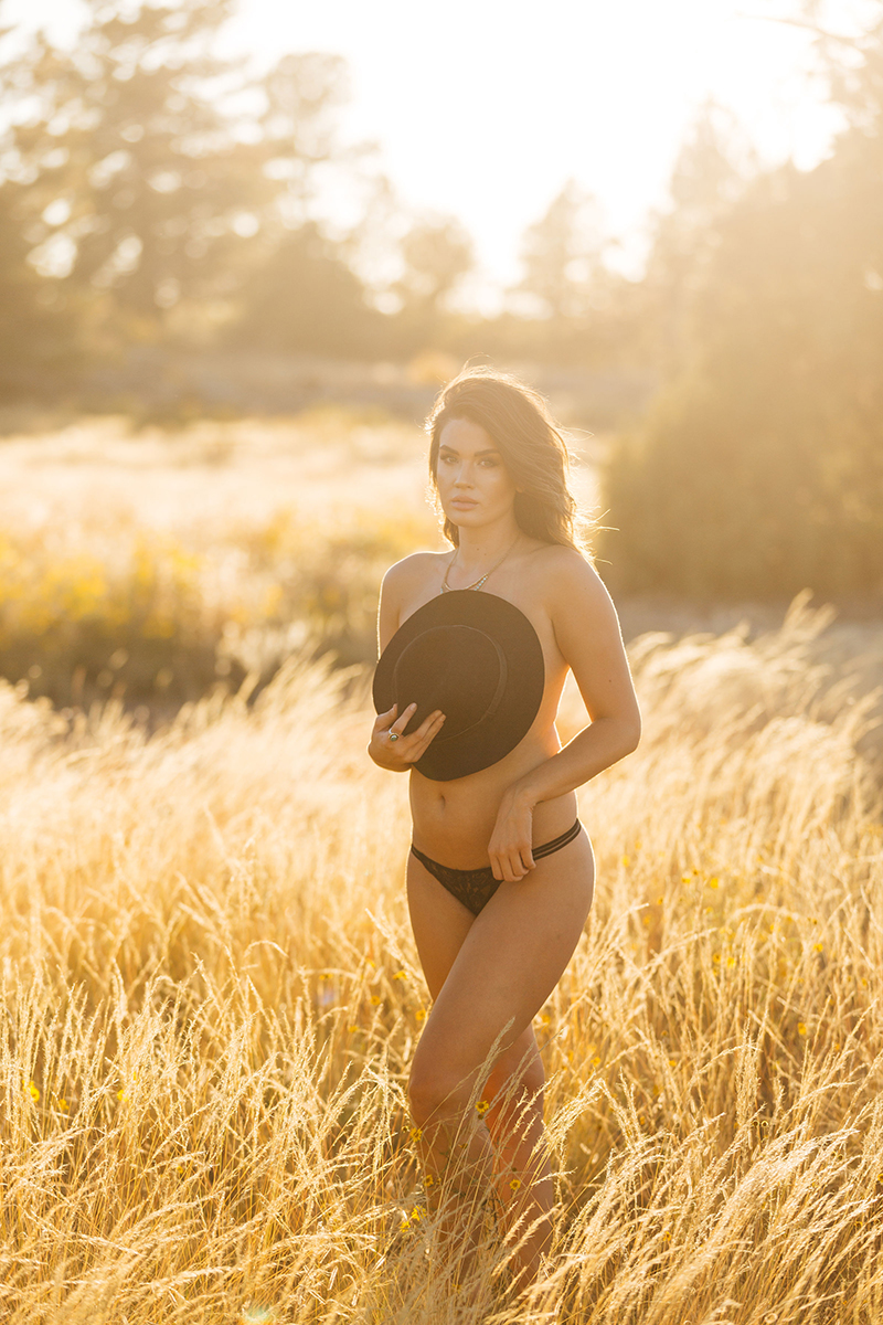 A beautiful young brunette woman poses topless for a Castlewood Canyon State Park boudoir photography session near Castle Rock, Colorado wearing black underwear and a black bohemian hat in the middle of a dry grass field at sunset