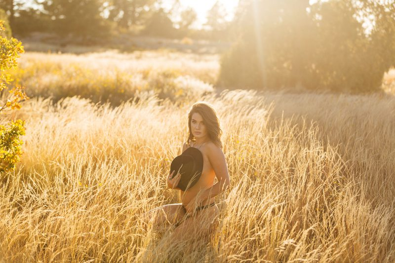 A beautiful young brunette woman poses topless for a Castlewood Canyon State Park boudoir photography session near Castle Rock, Colorado wearing black underwear and a black bohemian hat kneeling in the middle of a dry grass field at sunset