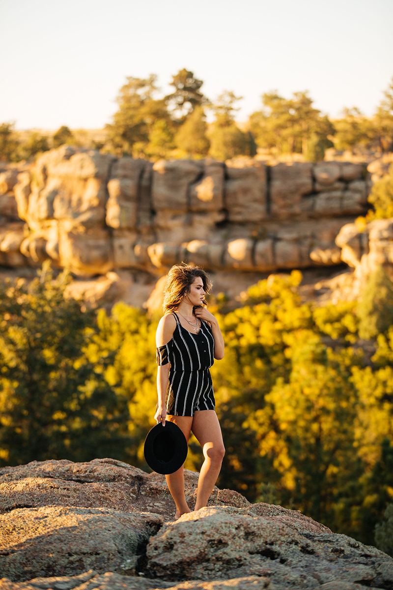 A beautiful young brunette woman poses for a Castlewood Canyon State Park boudoir photography session near Castle Rock, Colorado wearing black pinstripe dress and a black bohemian in front of a canyon at sunset