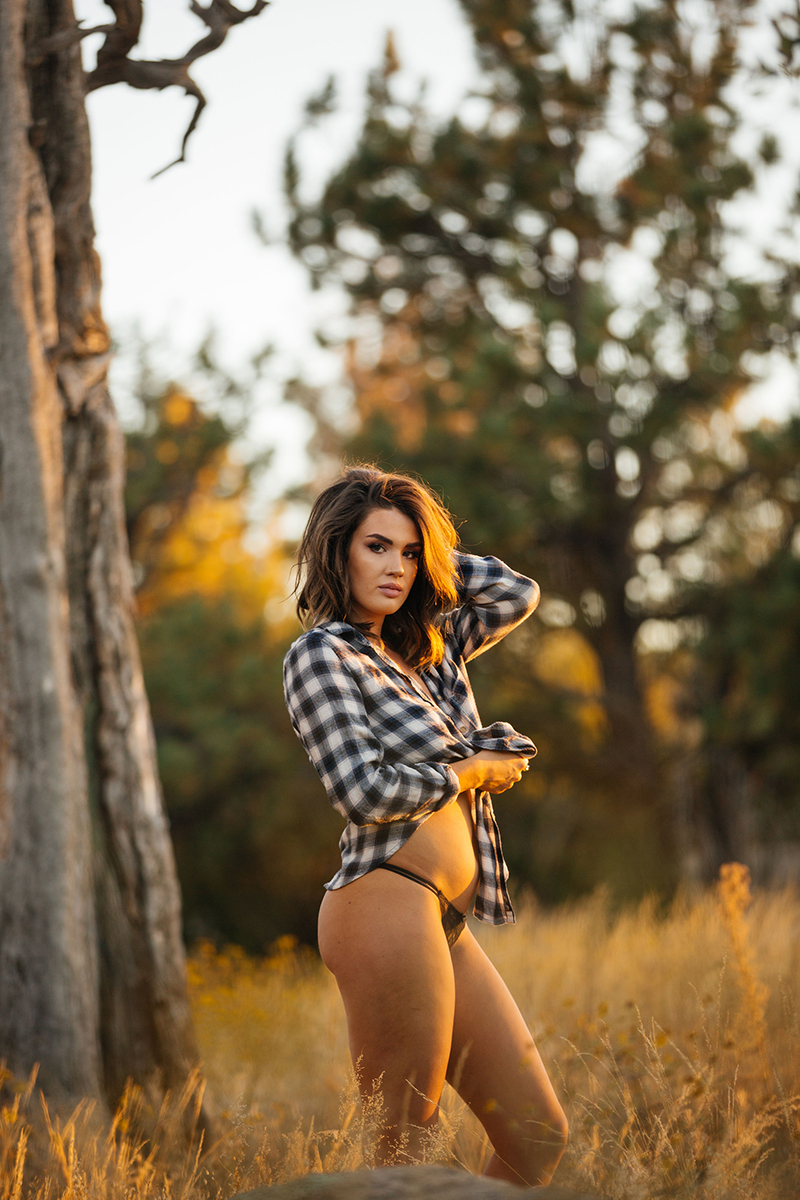 A beautiful young brunette woman poses topless for a Castlewood Canyon State Park boudoir photography session near Castle Rock, Colorado wearing black underwear and a black plaid button up shirt in front of tree in a grass field at sunset