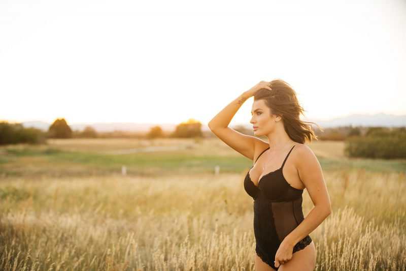 A beautiful young brunette woman poses for a Castlewood Canyon State Park boudoir photography session near Castle Rock, Colorado wearing black lingerie in a grass field at sunset