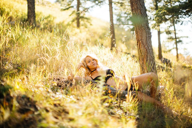 A beautiful young blonde woman poses for a Genesee Park boudoir photos session near Denver Colorado wearing a black bra and black underwear in a field on the side of a mountain as the sun sets