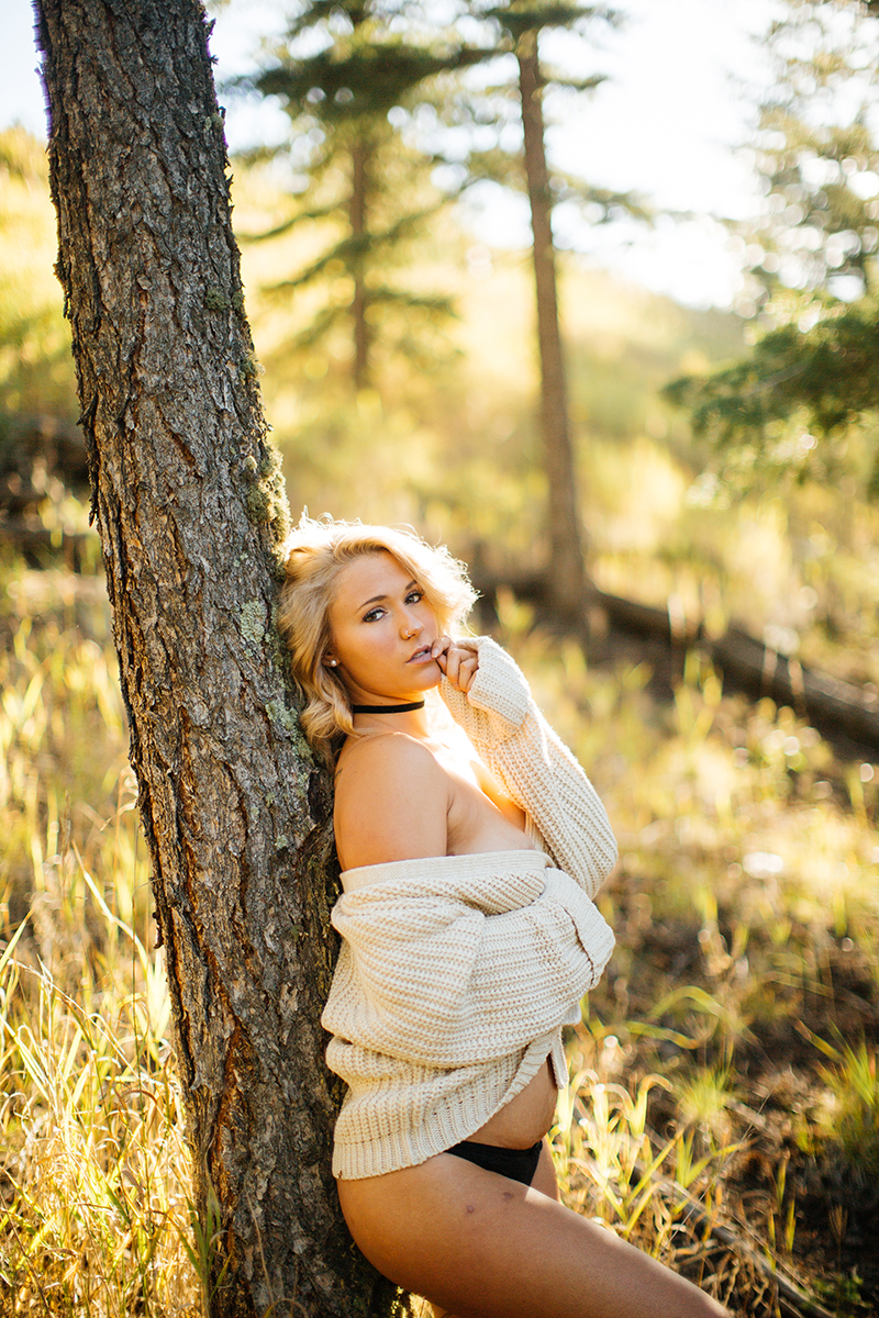 A beautiful young blonde woman poses topless for a Genesee Park boudoir photos session near Denver Colorado wearing a white sweater and black underwear leaning on a tree in a field on the side of a mountain as the sun sets