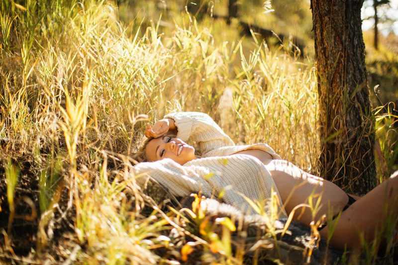 A beautiful young blonde woman poses topless for a Genesee Park boudoir photos session near Denver Colorado wearing a white sweater and black underwear laying in a field on the side of a mountain as the sun sets