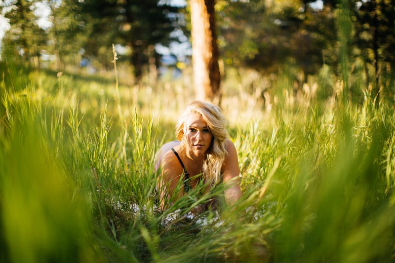 A beautiful young blonde woman poses for a Genesee Park boudoir photos session near Denver Colorado wearing purple lingerie in a field on the side of a mountain as the sun sets