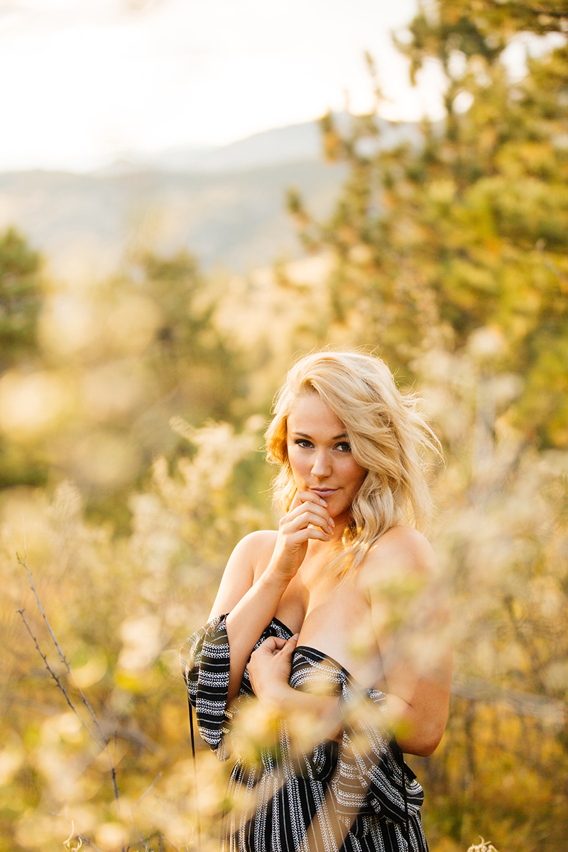 A beautiful young blonde woman poses for a Genesee Park boudoir photos session near Denver Colorado wearing a black and white striped shirt romper in a field on the side of a mountain as the sun sets