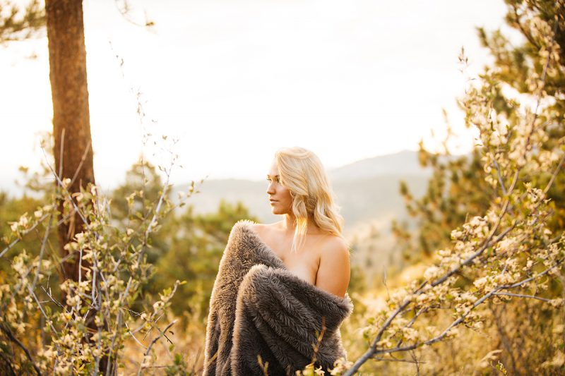 A beautiful young blonde woman poses topless for a Genesee Park boudoir photos session near Denver Colorado with a fur blanket wrapped around her in a field on the side of a mountain as the sun sets