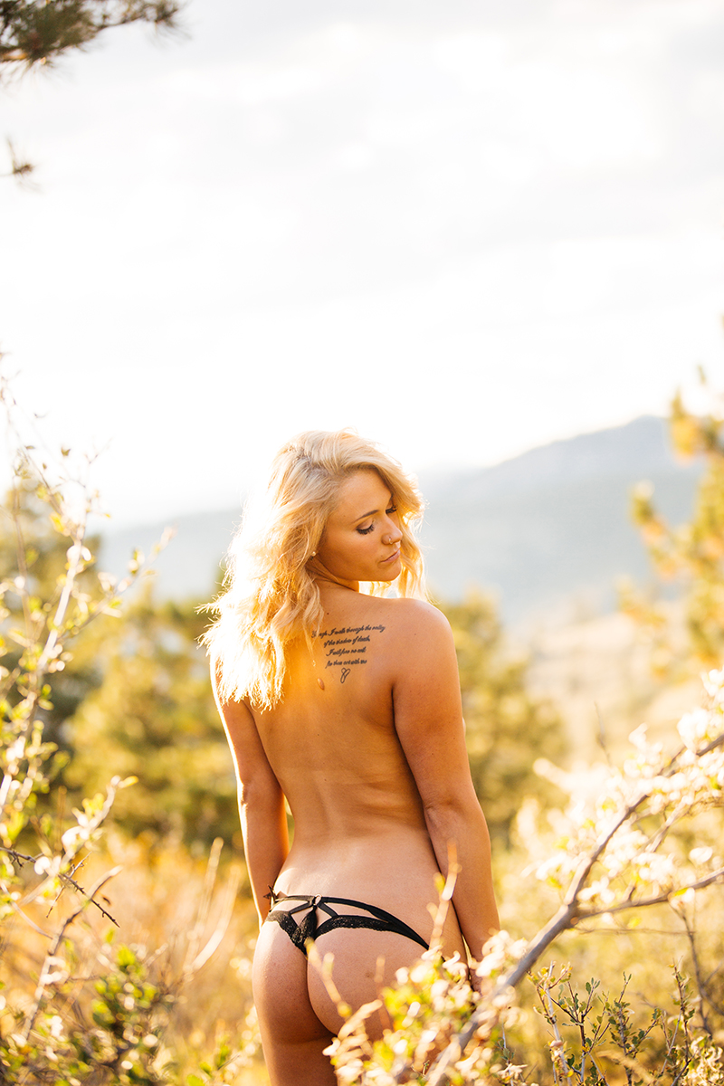 A beautiful young blonde woman poses topless for a Genesee Park boudoir photos session near Denver Colorado wearing black underwear in a field on the side of a mountain as the sun sets