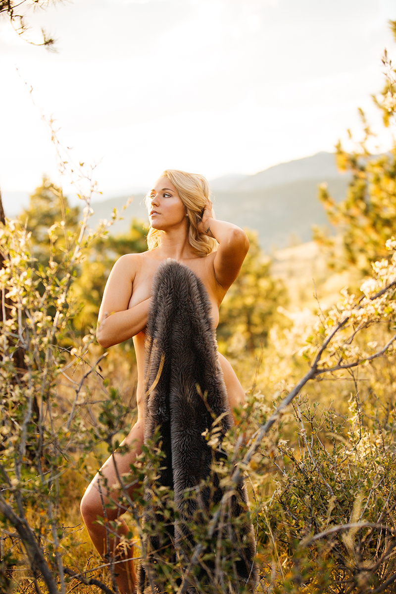 A beautiful young blonde woman poses nude for a Genesee Park boudoir photos session near Denver Colorado holding a fur blanket in a field on the side of a mountain as the sun sets