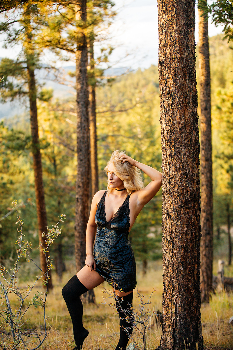 A beautiful young blonde woman poses for a Genesee Park boudoir photos session near Denver Colorado wearing black lingerie and black thigh high socks leaning against a tree in a field on the side of a mountain as the sun sets
