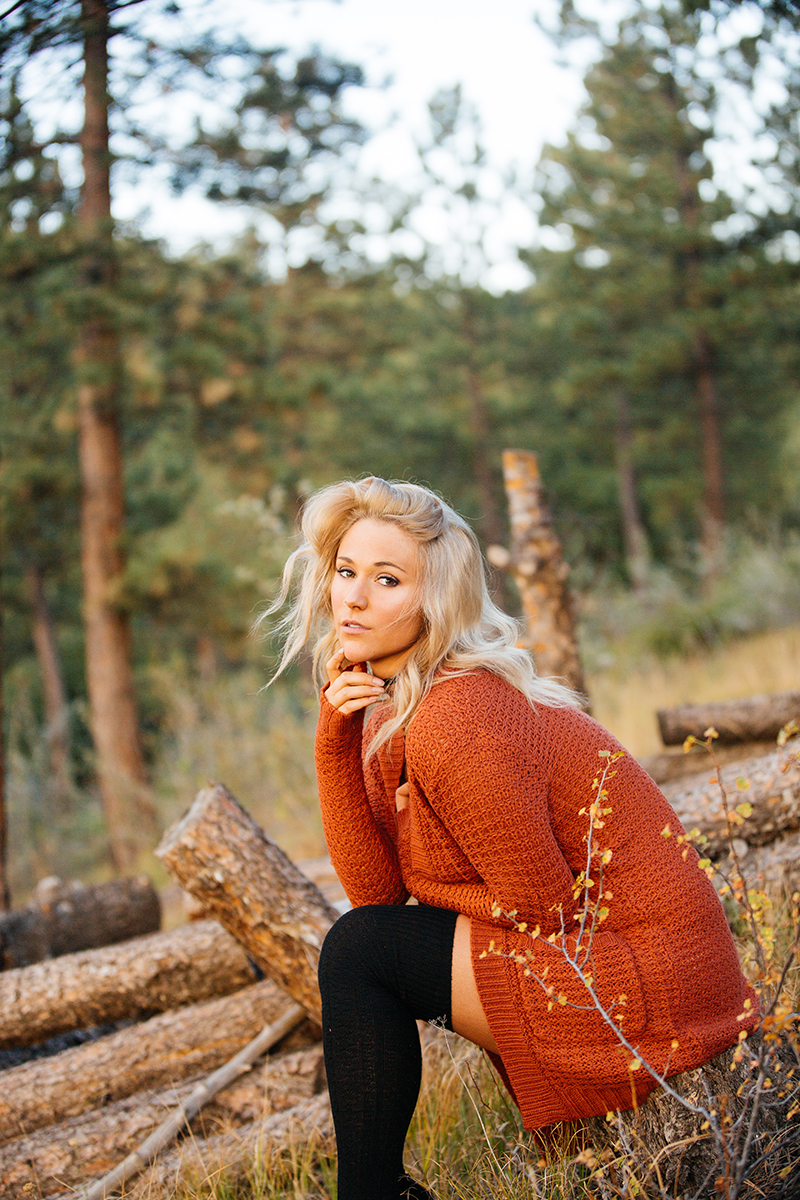 A beautiful young blonde woman poses topless for a Genesee Park boudoir photos session near Denver Colorado wearing an orange sweater, white underwear and black thigh high socks sitting on a fallen tree in a field on the side of a mountain as the sun sets