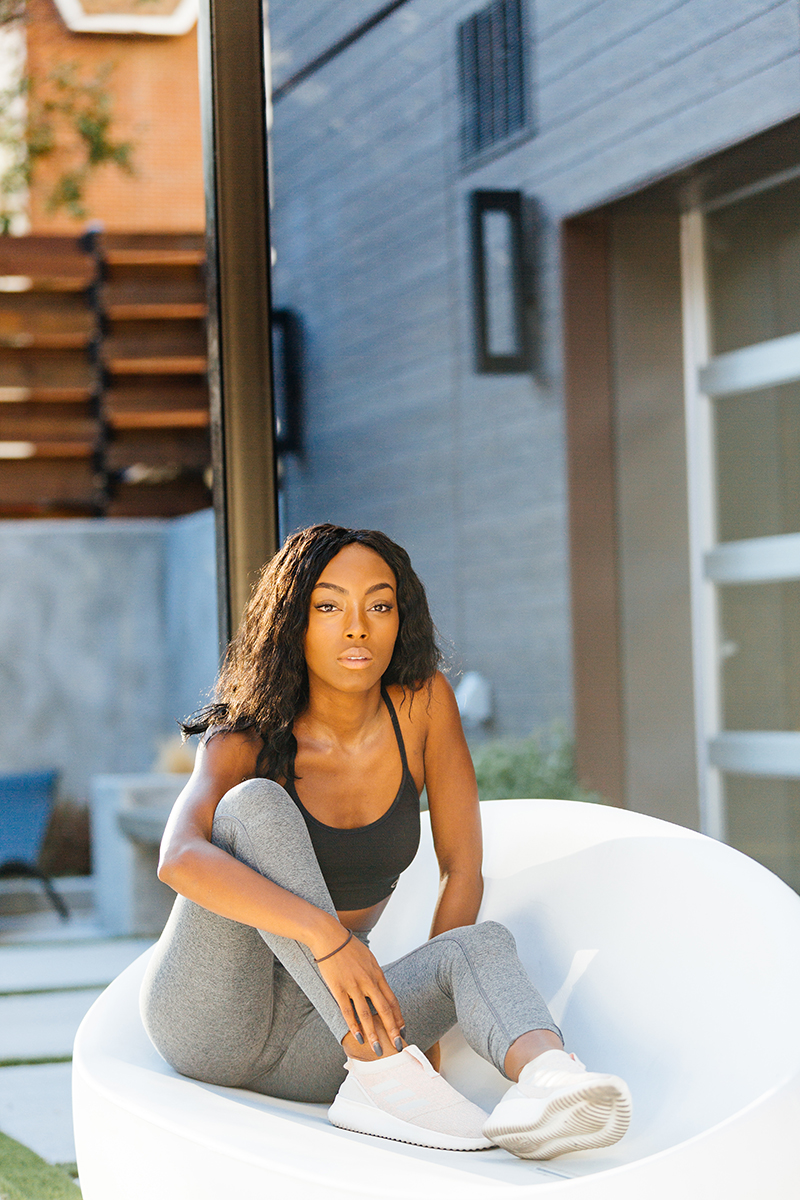 A beautiful African American woman poses for a Denver apartment fashion headshots session at her apartments in Cap Hill wearing gray workout leggings and a black sports bra sitting in a white chair on a modern outdoor patio