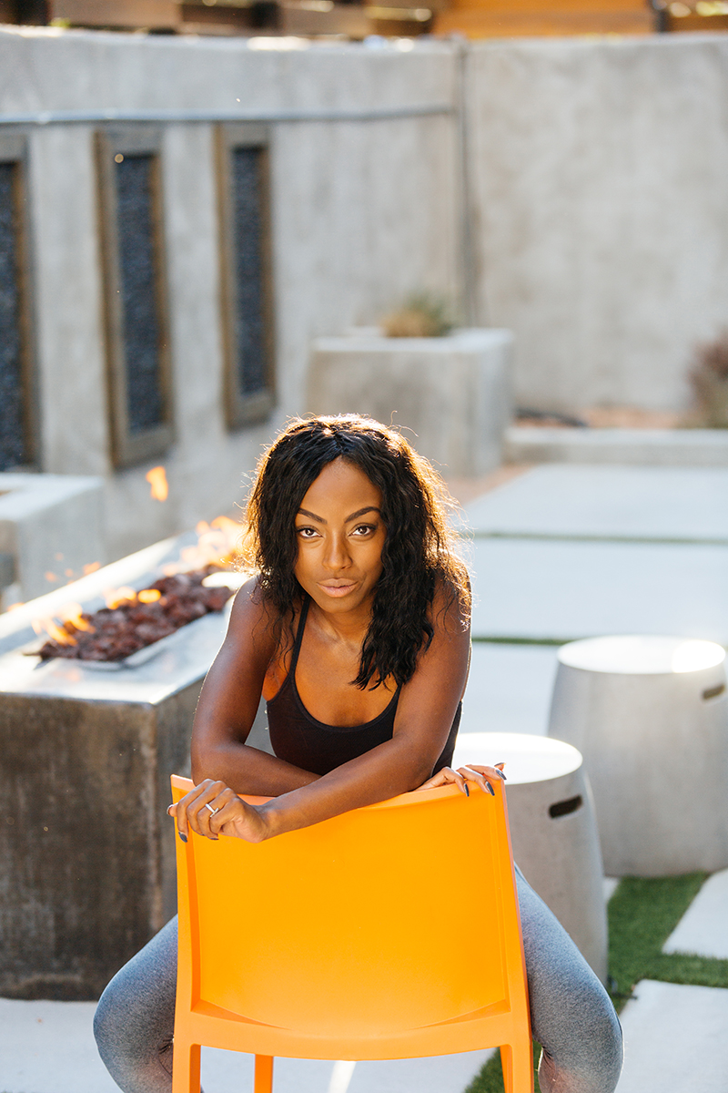 A beautiful African American woman poses for a Denver apartment fashion headshots session at her apartments in Cap Hill wearing gray workout leggings and a black sports bra sitting in n orange chair on a modern outdoor patio