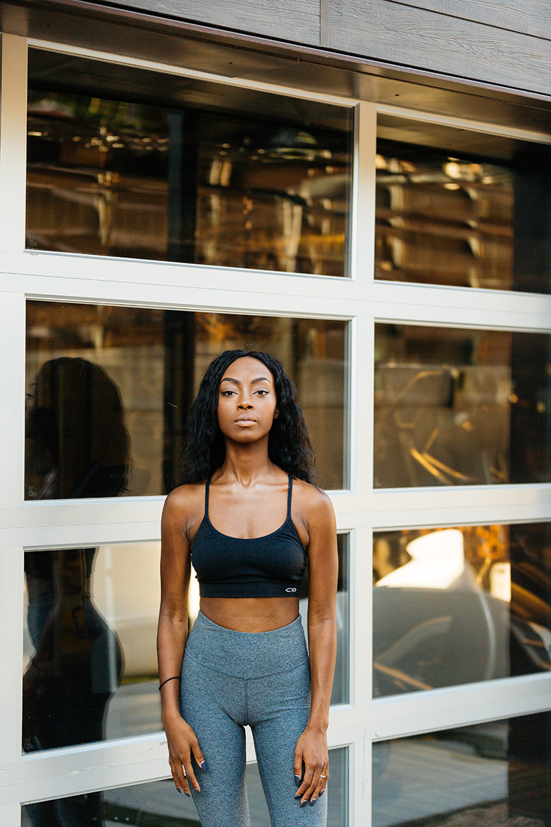 A beautiful African American woman poses for a Denver apartment fashion headshots session at her apartments in Cap Hill wearing gray workout leggings and a black sports bra standing in front of a window on a modern outdoor patio