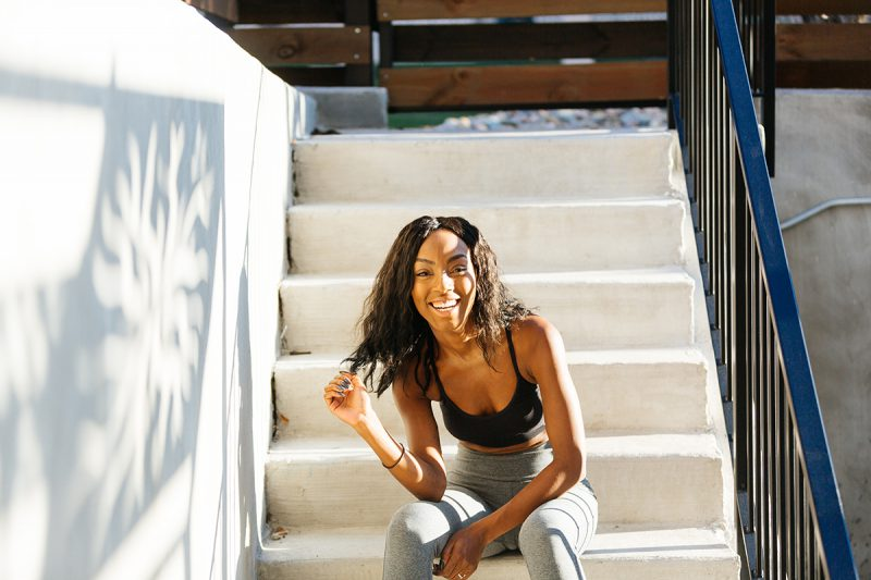 A beautiful African American woman poses for a Denver apartment fashion headshots session at her apartments in Cap Hill wearing gray workout leggings and a black sports bra sitting on concrete stairs at a modern outdoor patio