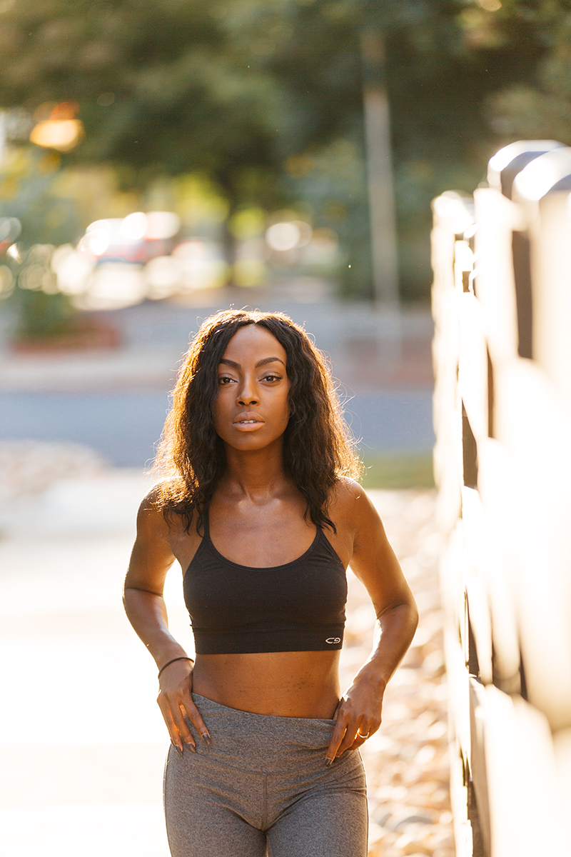 A beautiful African American woman poses for a Denver apartment fashion headshots session at her apartments in Cap Hill wearing gray workout leggings and a black sports walking on the sidewalk