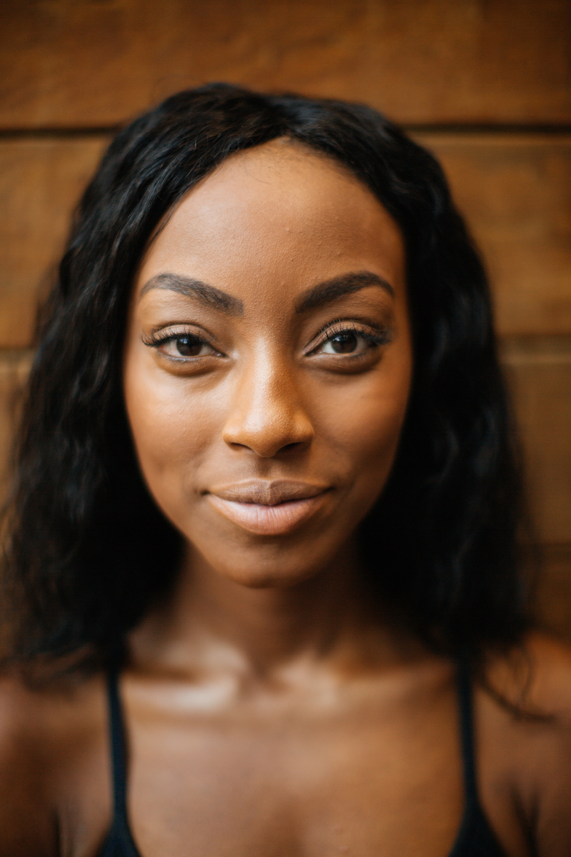 A beautiful African American woman poses for a Denver apartment fashion headshots session at her apartments in Cap Hill wearing gray workout leggings and a black sports bra leaning against a wood wall
