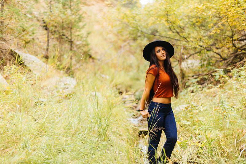 A beautiful young brunette woman poses for a Genesee Park boudoir photos session near Denver, Colorado in the Rocky Mountains wearing an orange shirt, blue jeans and a black bohemian hat in a field near a creek