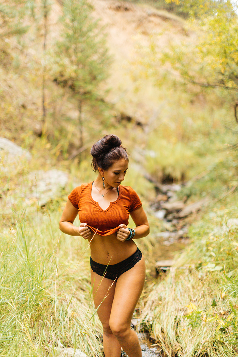 A beautiful young brunette woman poses for a Genesee Park boudoir photos session near Denver, Colorado in the Rocky Mountains wearing an orange shirt and black underwear in a field near a creek
